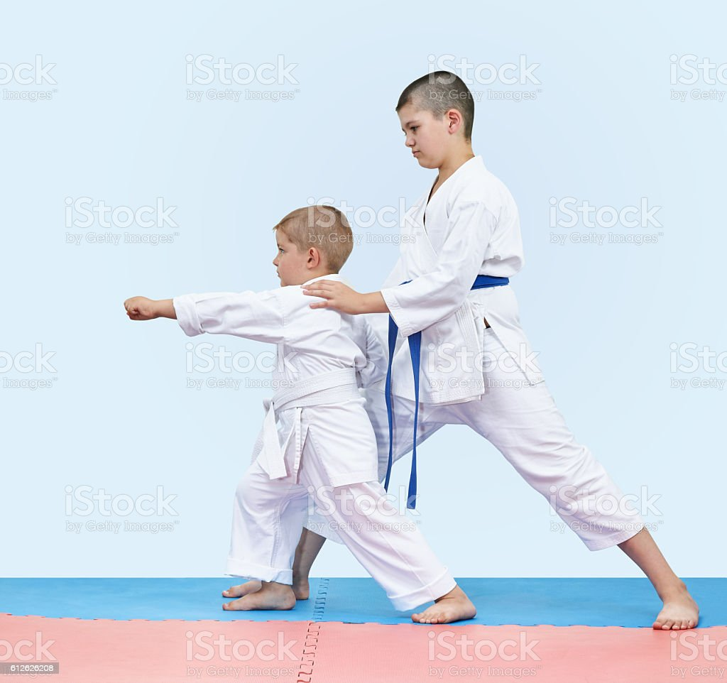 Elder brother teaches junior beat punch arm stock photo