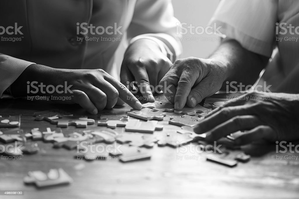 Elder care nurse playing jigsaw puzzle with senior man stock photo