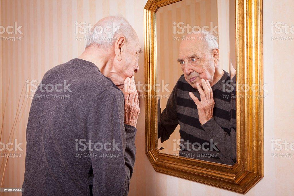 elder man looking at himself at the mirror stock photo