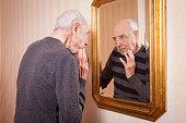 elder man looking at himself at the mirror