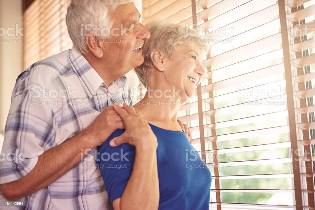 Elder marriage looking through the window stock photo