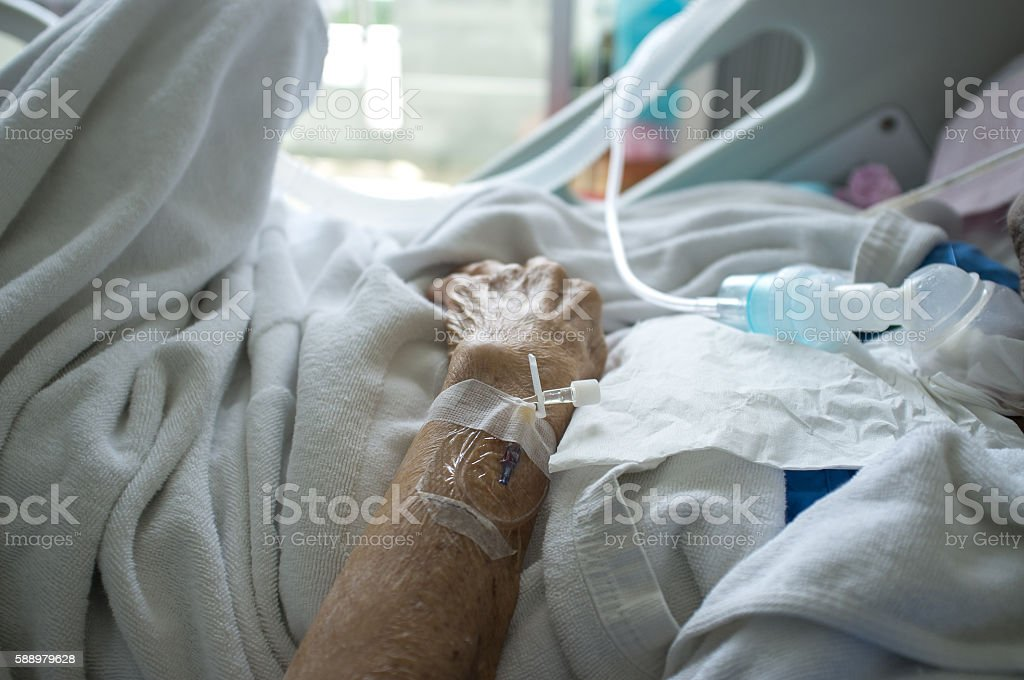 Elder patient's hand and blood test tube stock photo