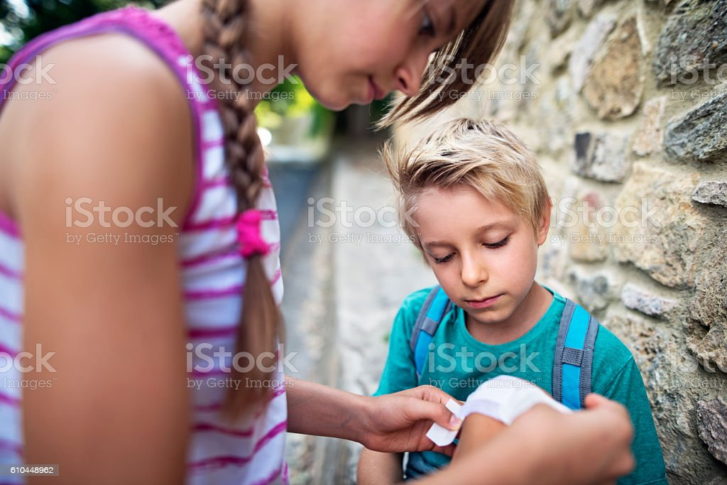 Elder sister tending to her little brother's wounded knee stock photo