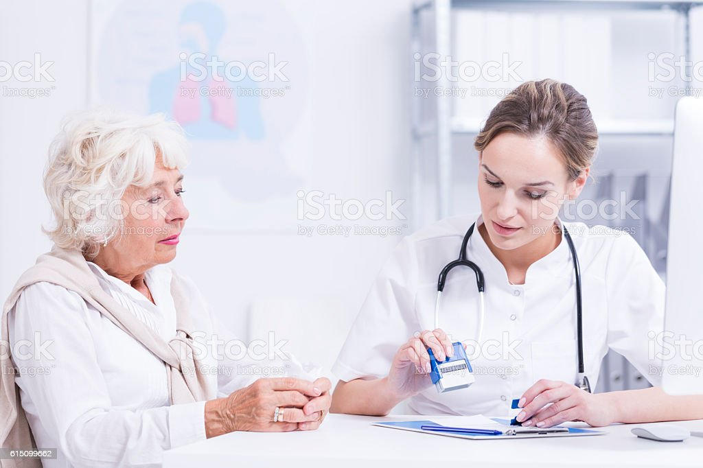 Elder woman and young doctor stock photo