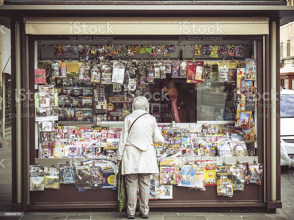 Elder Woman Buying Magazine at Italian News Stand stock photo
