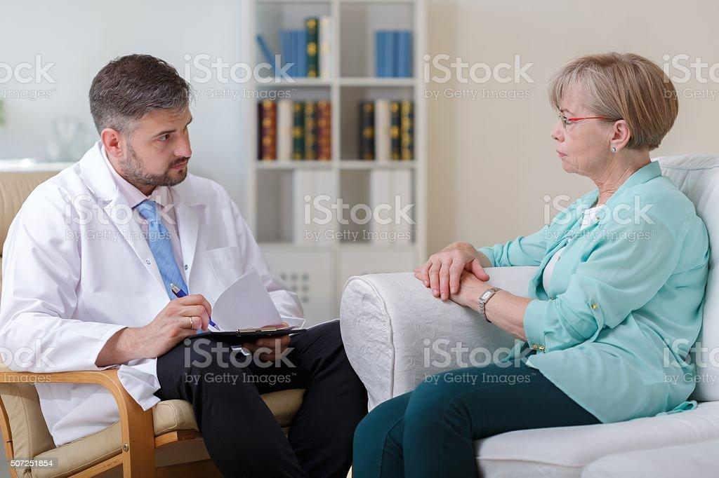 Elder woman talking with psychologist stock photo