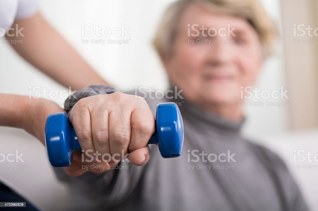 Elder woman training with physiotherapist stock photo