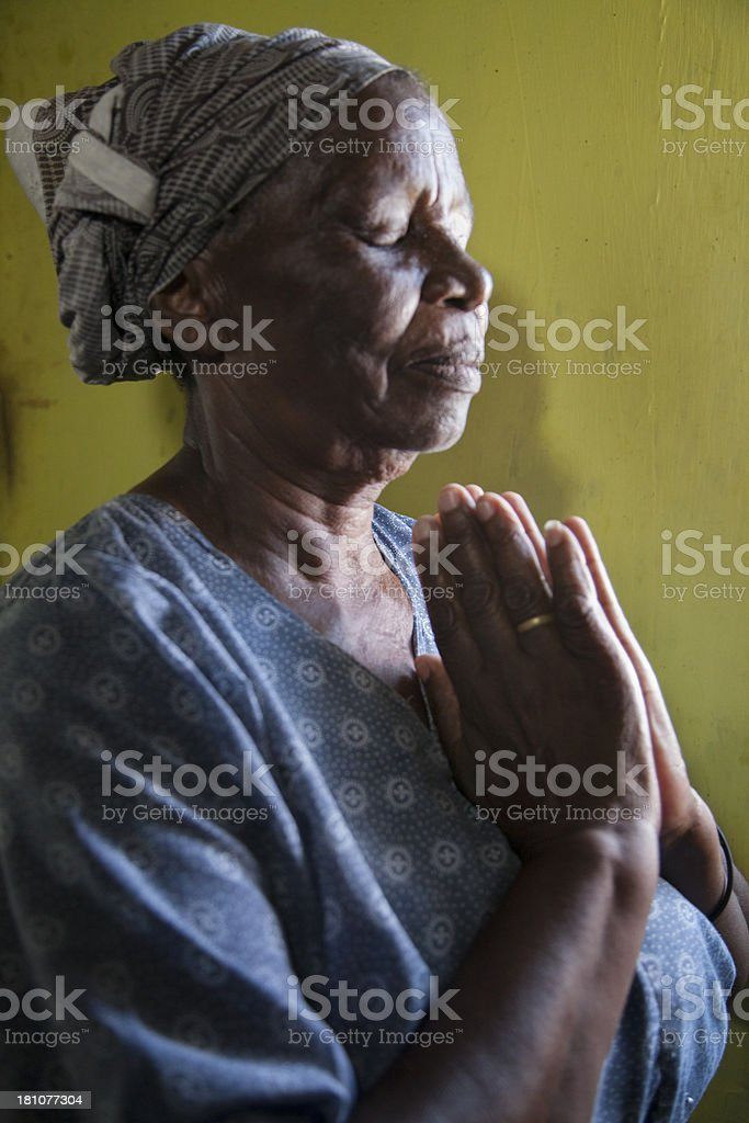 Elderly African Woman Praying , Gugulethu, Cape Town, South Africa. royalty-free stock photo