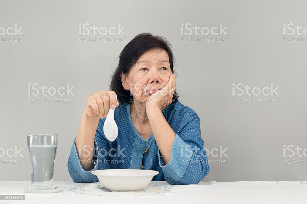 Elderly asian woman bored with food stock photo