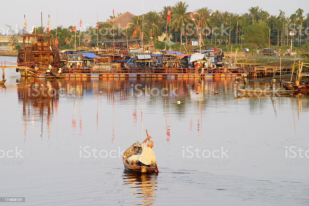 Elderly boatman rowing on Hoi An river at sunset stock photo
