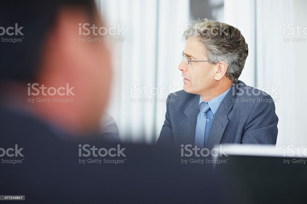Elderly business man at a meeting with colleagues royalty-free stock photo