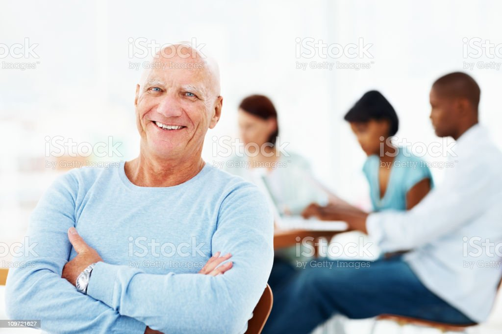 Elderly business man with hands folded and his team royalty-free stock photo