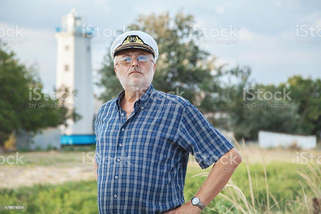 Elderly captain on the sea shore stock photo