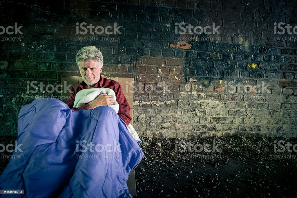 Elderly caucasian homeless man with sleeping bag in subway tunnel stock photo
