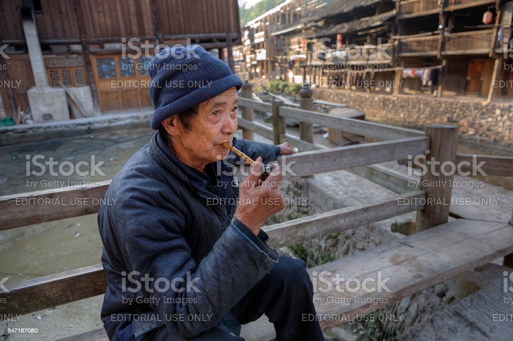 Elderly chinese man holds in his hand bamboo pipe smoking. stock photo