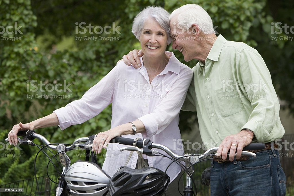 Elderly couple about to ride their bicycle royalty-free stock photo