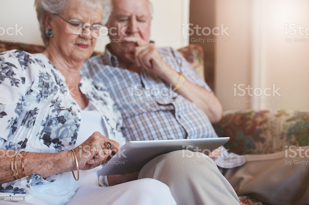 Elderly couple at home using digital tablet stock photo