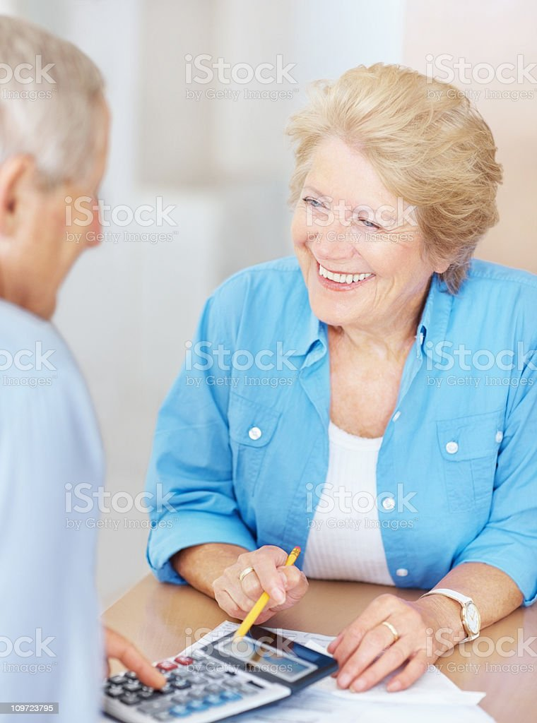 Elderly couple calculating their personal finances at home royalty-free stock photo