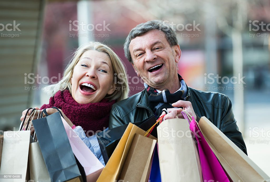 Elderly couple carrying purchases in city stock photo