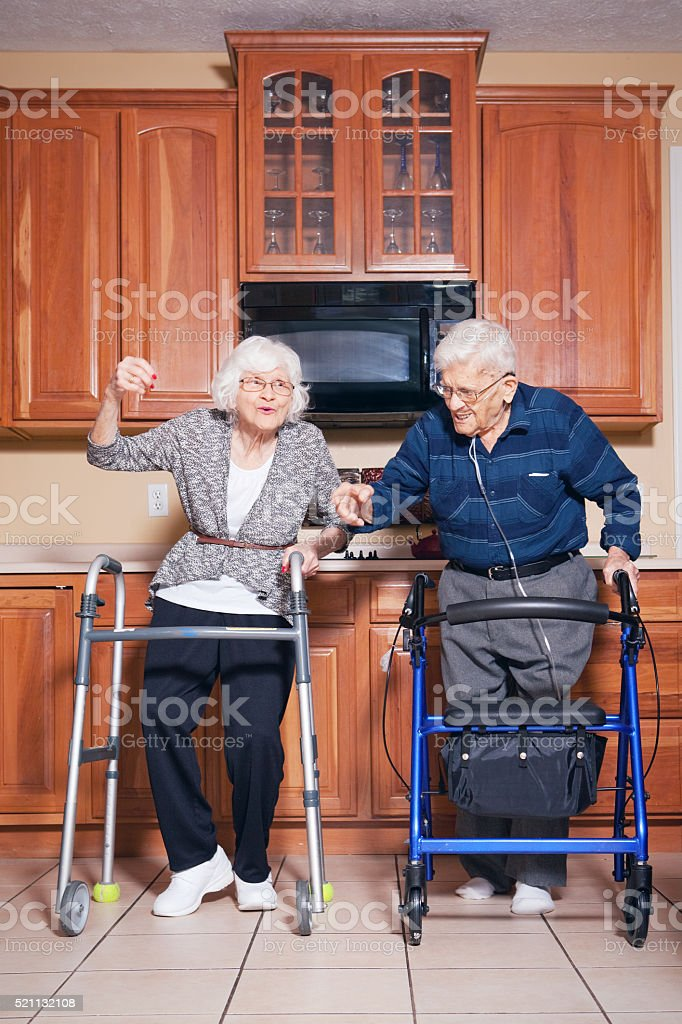 Elderly Couple Dancing In Kitchen Together stock photo