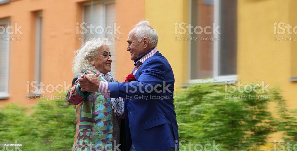 Elderly couple dancing on the street. Waltz outdoors. True love. stock photo