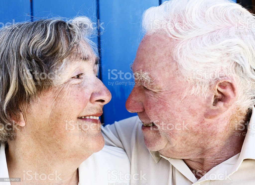 Elderly couple embrace and smile at each other stock photo