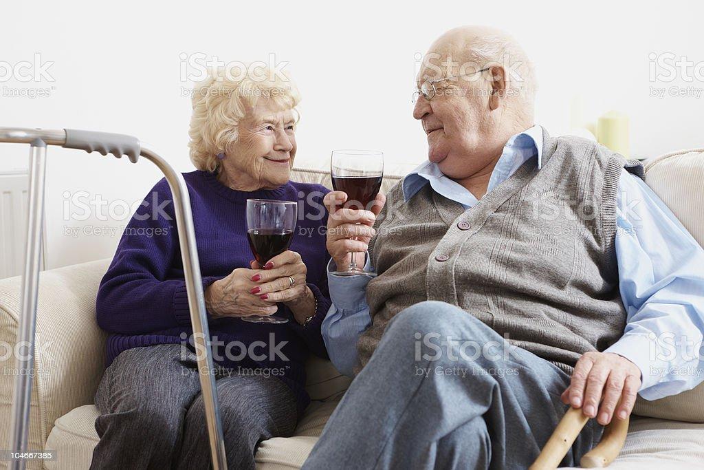 elderly couple enjoying a glass of wine royalty-free stock photo