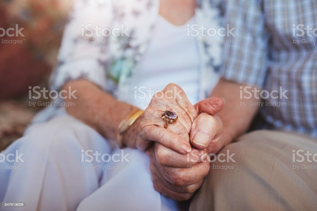 Elderly couple holding hands stock photo