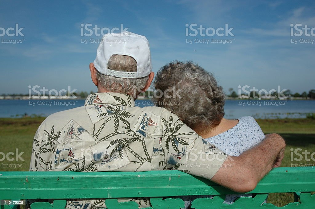 Elderly couple in love and enjoying a lake view stock photo