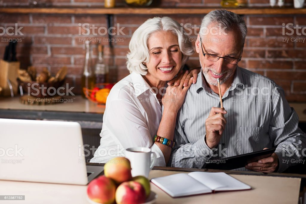 Elderly couple making notes in a kitchen stock photo