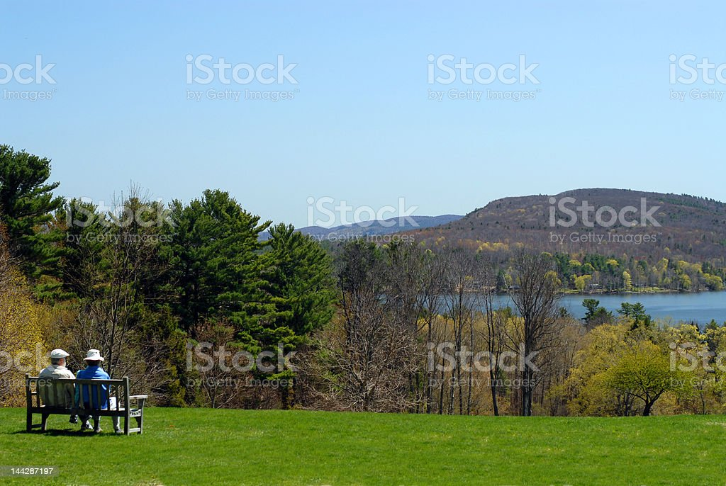 Elderly Couple on Bench Looking out at Lake stock photo