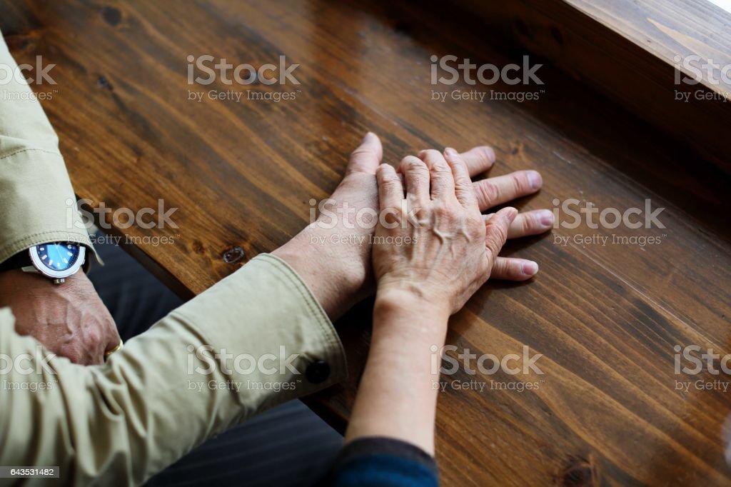 Elderly couple overlaying the hand stock photo