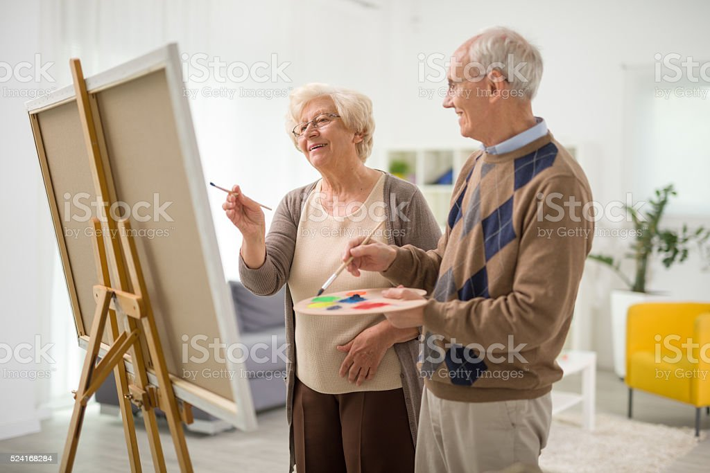 Elderly couple painting on a canvas stock photo