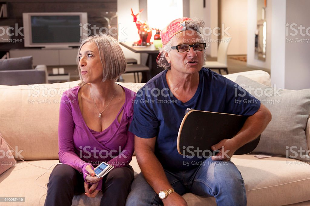 elderly couple playing at being young at home stock photo