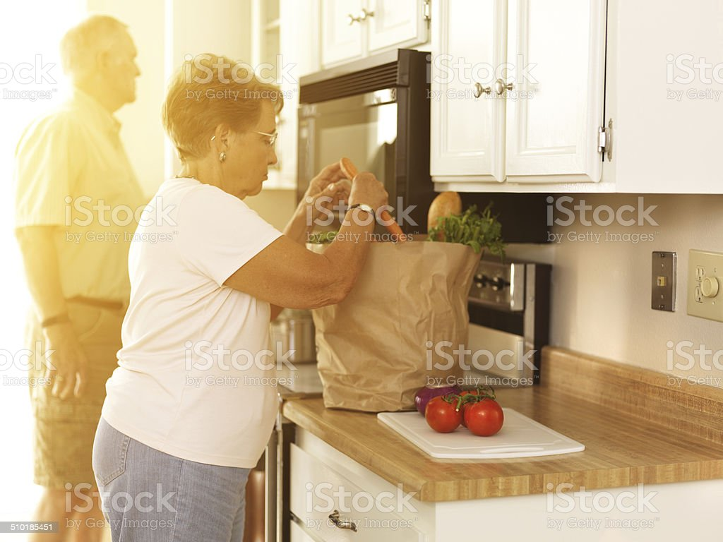 Elderly couple putting away groceries at home stock photo