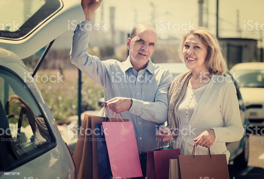 Elderly couple putting bags  in trunk stock photo