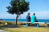 Elderly couple rest and look at scenic ocean view