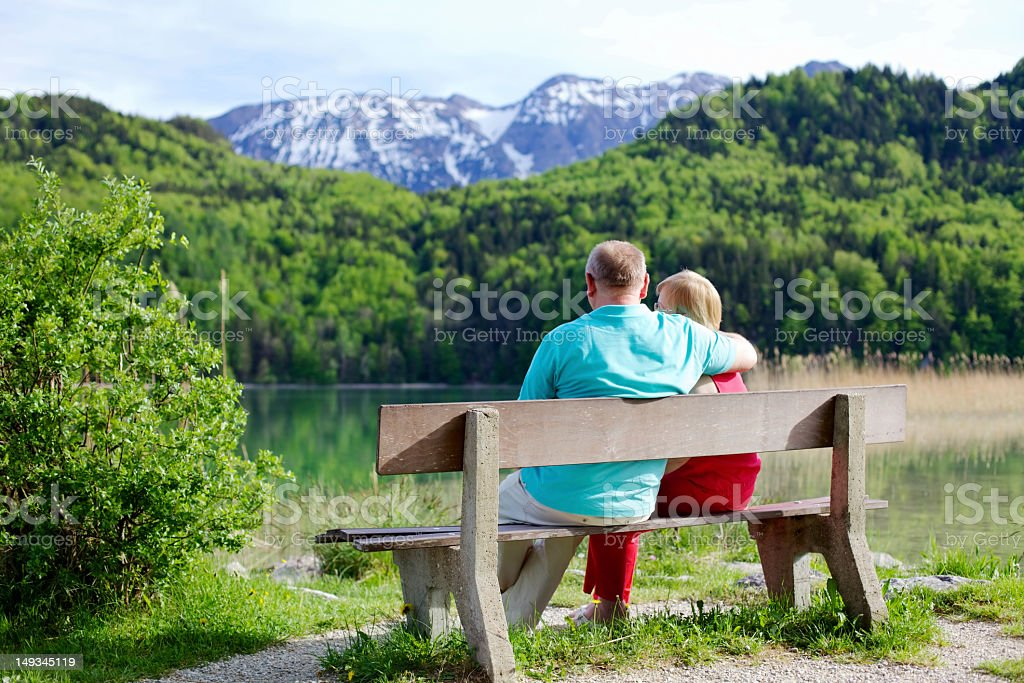 Elderly couple rests on bench royalty-free stock photo