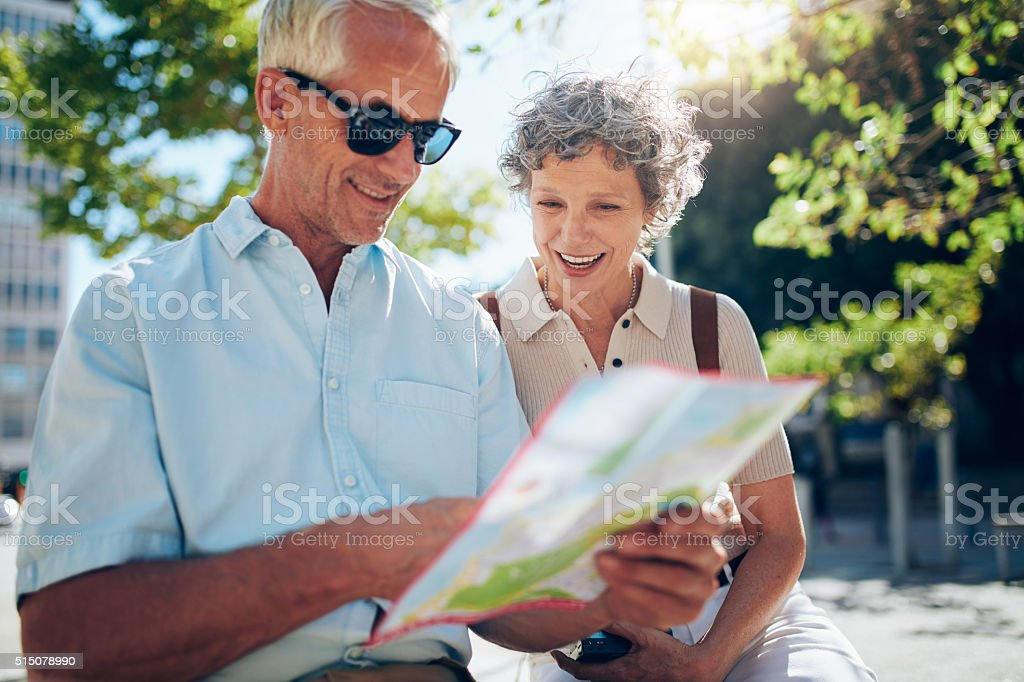 Elderly couple sitting on a bench and using city map stock photo
