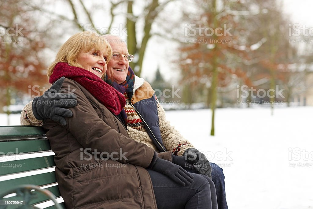 Elderly couple sitting on a bench at snow park royalty-free stock photo