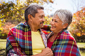 Elderly couple sitting on bench smiling at each other
