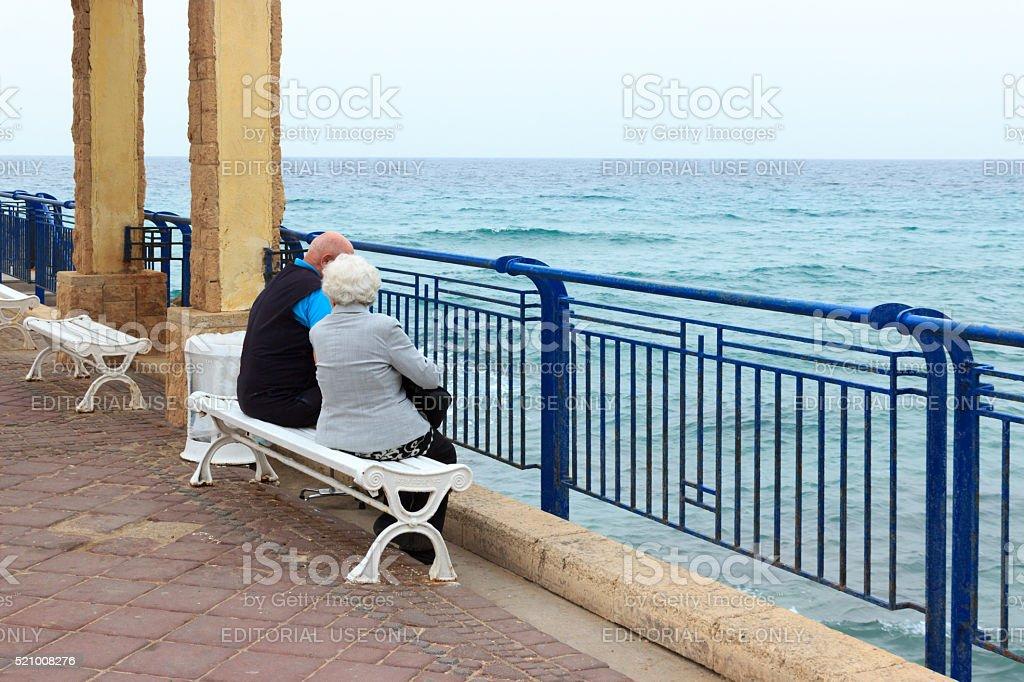 Elderly couple sitting on the sea at Nahariya's promenade. stock photo