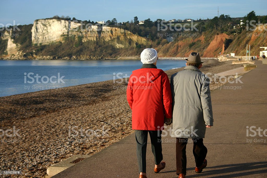 Elderly couple stroll the promenade royalty-free stock photo