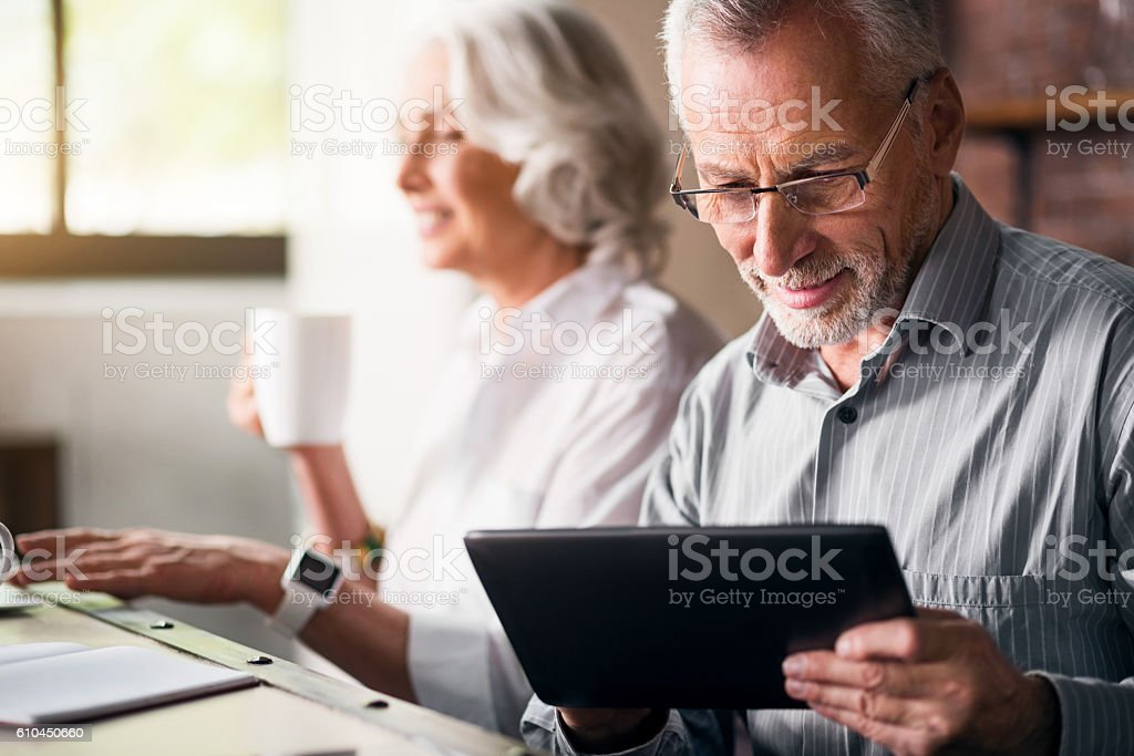 Elderly couple together at the kitchen stock photo