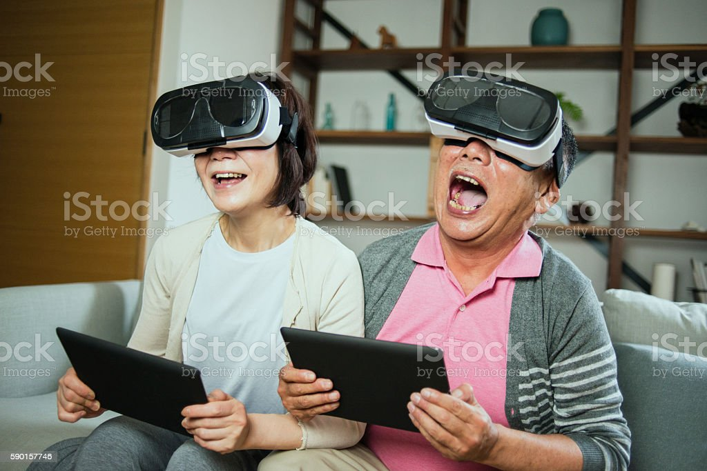 Elderly couple trying out some virtual reality headsets stock photo