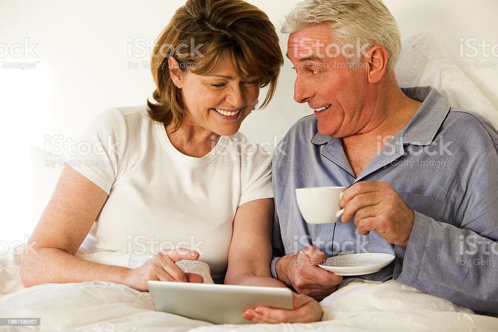 Elderly Couple Using Laptop In Bed royalty-free stock photo