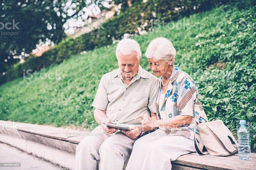 Elderly couple using tablet computer outdoor stock photo
