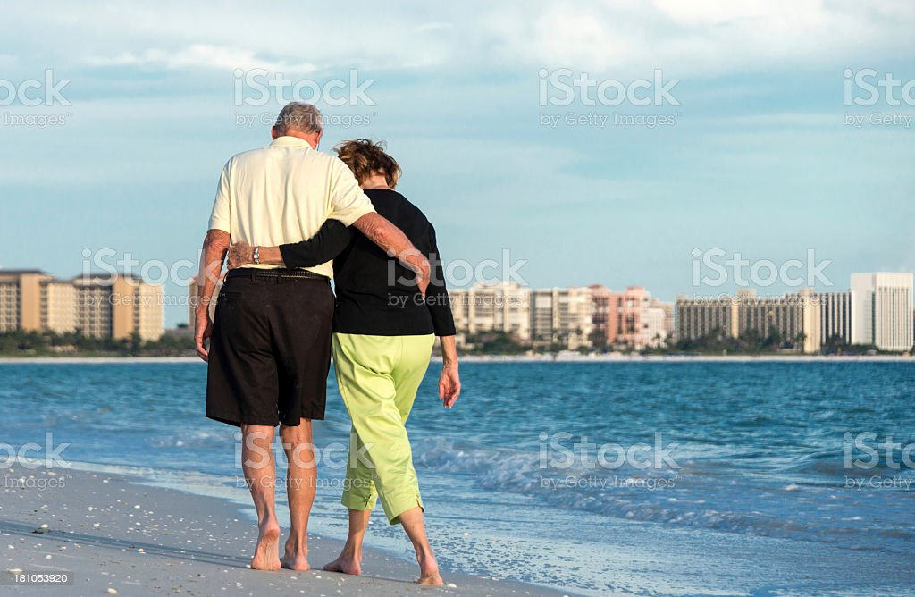 Elderly couple walking about the beach stock photo