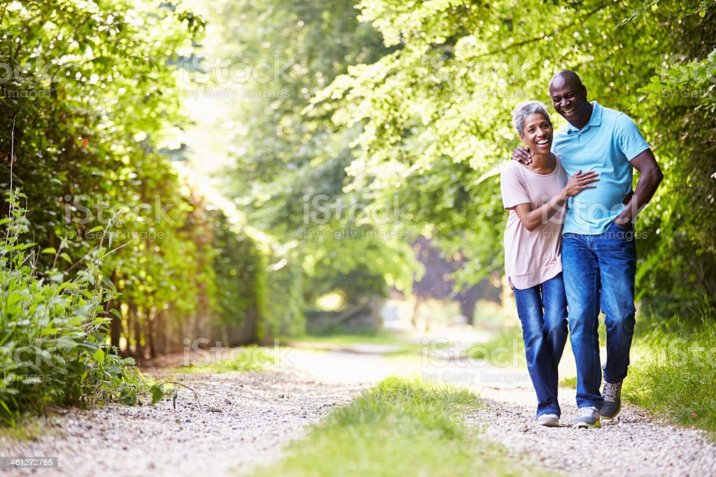 Elderly couple walking along a gravel path with trees stock photo