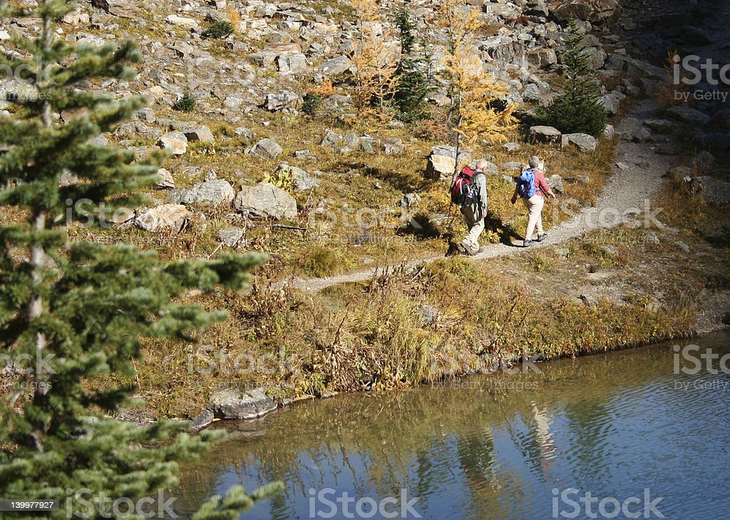 elderly couple walking beside Lake Agnes Canadian Rockies stock photo